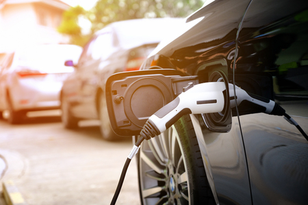 Photo for Charging modern electric car battery on the street which are the future of the Automobile, Close up of power supply plugged into an electric car being charged for hybrid . New era of vehicle fuel. - Royalty Free Image