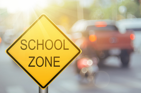 Photo for School zone warning sign on blur traffic road with colorful bokeh light abstract background. Copy space of transportation and travel concept. Vintage tone filter color style. - Royalty Free Image