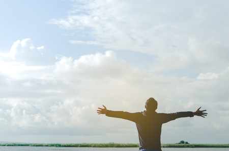 Photo for Feel good freedom and travel adventure concept. Copy space of happy man raise hands on river and blue sky white cloud background. Vintage tone filter effect color style. - Royalty Free Image
