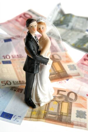 Wedding couple figurine over euro notes background, love and money