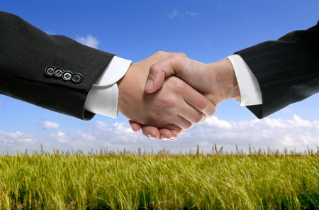 Businessman teamwork partners shaking hands in green nature