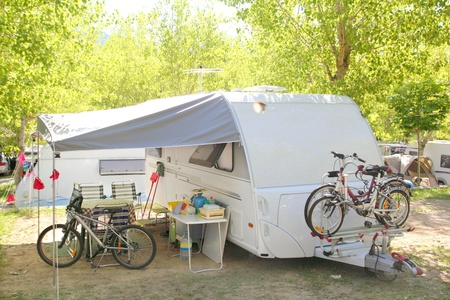 Camping camper caravan trees park with bicycles