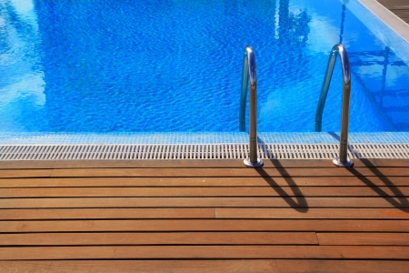 blue swimming pool with teak wood flooring deck summer vacation concept