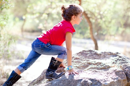 Hiking little girl climbing a rock in forest outdoor