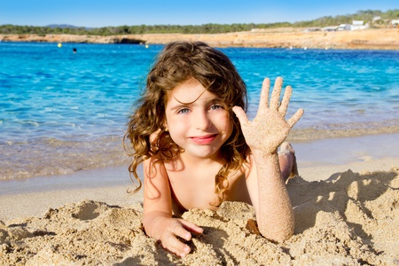 Little girl greeting hand gesture in sandy beach of Ibiza Cala Conta