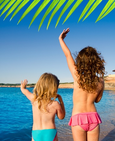 Photo for Ibiza Cala Conta beach little girls greeting hand sign saying bye - Royalty Free Image