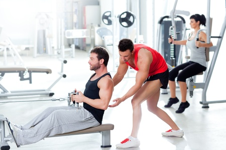 man in gym with personal trainer and fitness woman
