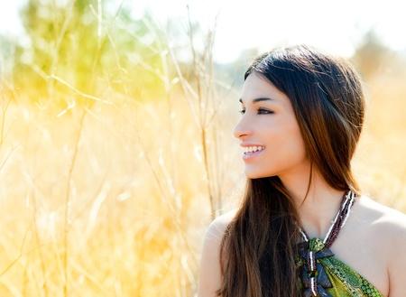 Asian indian woman profile portrait in golden grass field