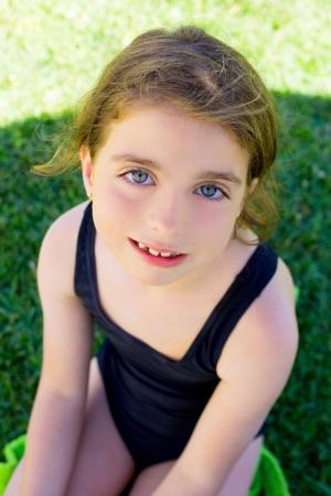 brunette children girl smiling with black swimming suit on garden grass