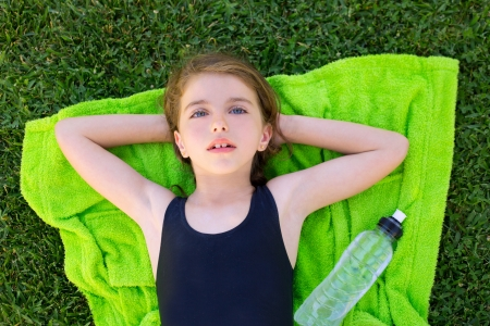 children girl relaxed lying on towel over green grass with water bottle in swimsuit