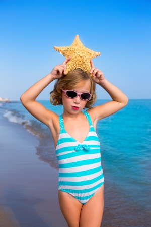 Photo for child kid girl in summer beach vacations with starfish and aqua sea - Royalty Free Image