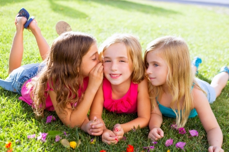 children friend girls group playing whispering on flowers grass in vacations