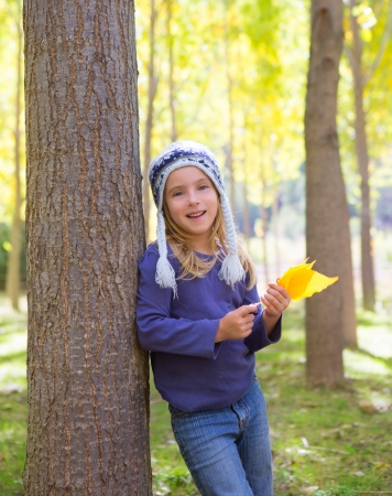 Child girl in autumn poplar forest with yellow fall leaves in hand smiling happy outdoor