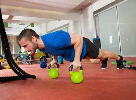 Photo for Crossfit fitness man push ups Kettlebells pushup exercise at gym workout - Royalty Free Image