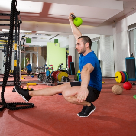 Photo for Crossfit fitness man balance Kettlebells with one leg exercise at gym workout - Royalty Free Image