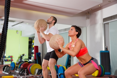 Photo for Crossfit ball fitness workout group woman and man at gym - Royalty Free Image