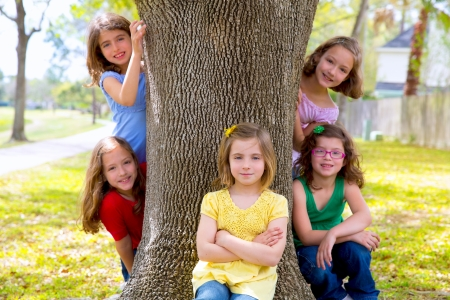 Photo for Children group of sisters girls and friends playing on tree trunk at the park outdoor - Royalty Free Image