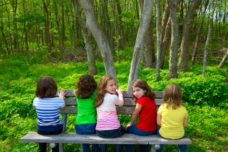 Photo pour Children sister and friend girls sitting on park bench looking at forest and smiling - image libre de droit