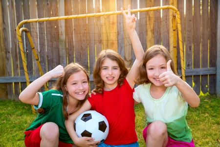 Photo for three sister girls friends soccer football winner players on the backyard - Royalty Free Image