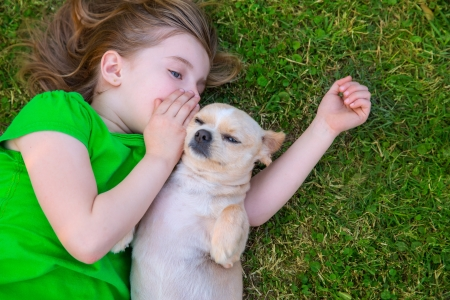 Blond happy girl with her chihuahua doggy portrait lying on lawn