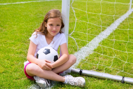 Photo pour Soccer football kid girl relaxed on grass lawn with ball - image libre de droit