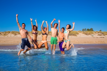Foto de Happy excited teen boys and girls group jumping at the beach splashing water - Imagen libre de derechos