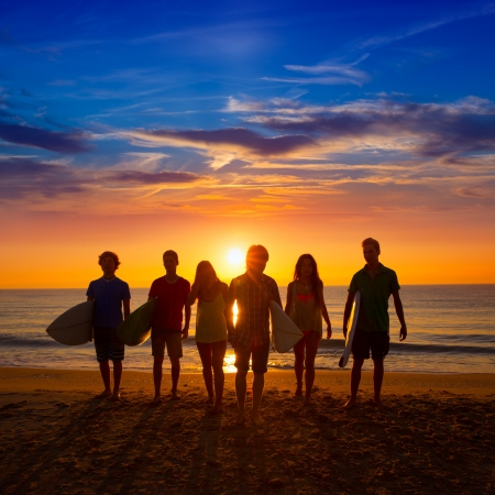 Photo for Surfers teen boys and girls group walking on beach at sunshine sunset backlight - Royalty Free Image