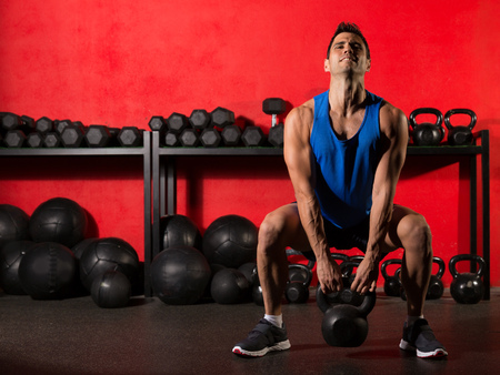 Photo for Kettlebell swing workout training man at gym with red walls - Royalty Free Image