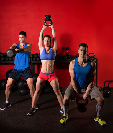Photo for Kettlebell swing workout training group at gym with red wall - Royalty Free Image