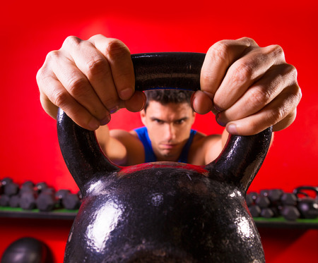 Photo for Kettlebell man portrait looking through the handle ring at gym workout - Royalty Free Image