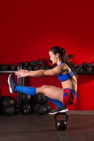 Photo for kettlebell woman pistol squat workout balance in red gym - Royalty Free Image