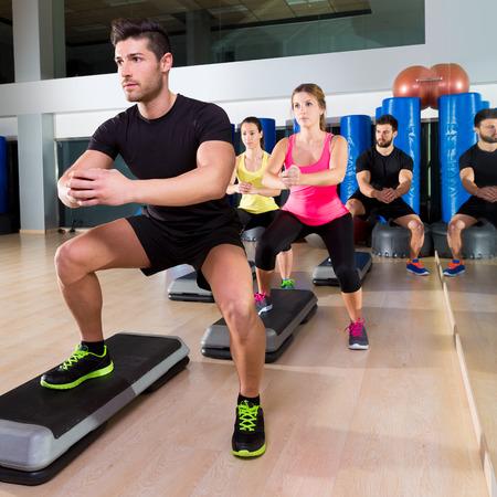 Foto de Cardio step dance squat people group at fitness gym training workout - Imagen libre de derechos