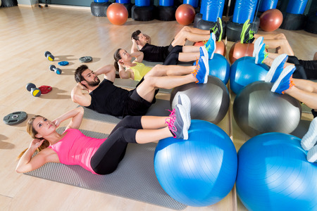 Foto de Fitball crunch training group core fitness at gym abdominal workout - Imagen libre de derechos
