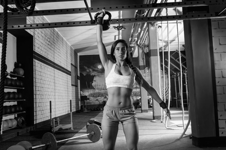 Photo for brunette girl at gym lifting a kettlebell weightlifting workout - Royalty Free Image