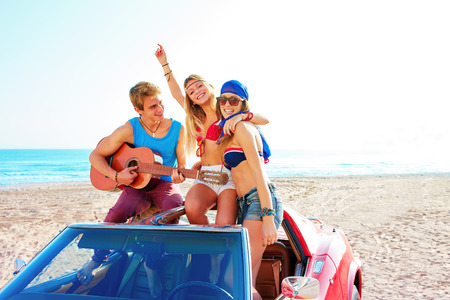 Photo for young group having fun on the beach playing guitar and dancing in a convertible car - Royalty Free Image