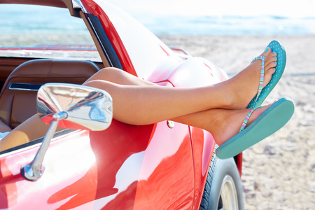 Photo pour Relaxed woman legs and flip flops in a car window on the beach - image libre de droit