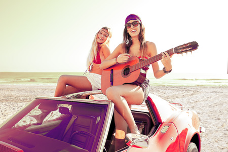 Photo for girls having fun playing guitar on th beach with a convertible car - Royalty Free Image