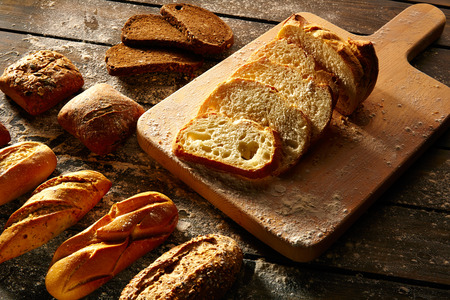 Photo pour Bread varied loafs sliced on wood board in rustic wood table - image libre de droit