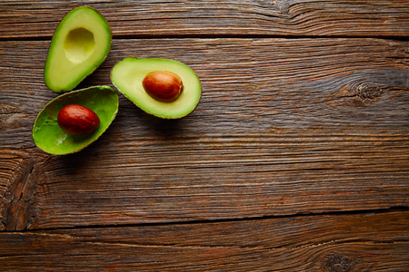 Photo for avocado cut on aged wood table board cutted half - Royalty Free Image