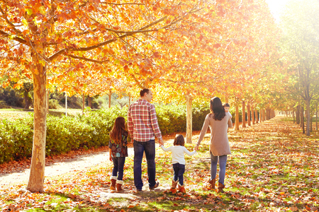 Photo for family walking in an autumn park with fallen fall leaves - Royalty Free Image