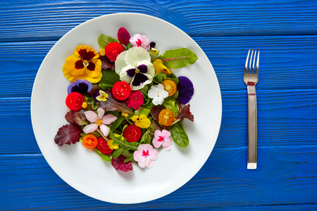 Photo for Edible flowers salad in a plate on blue wooden table with fork - Royalty Free Image