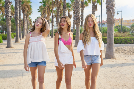Teen best friends girls group walking happy in a palm trees beach area