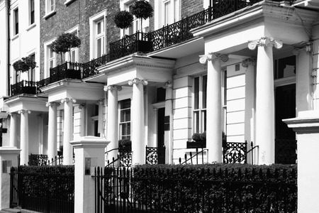 Black and white monochrome photograph picture of expensive old fashioned typical Regency Georgian terraced town houses building architecture in fashionable Notting Hill, Kensington, London, England, UK