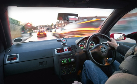 Photo for A man speeding in a car in a built up area. - Royalty Free Image