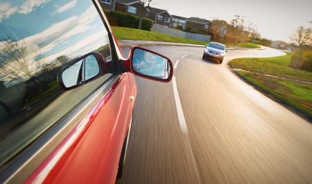 Photo for A man driving a red car towards a bend in the road. - Royalty Free Image