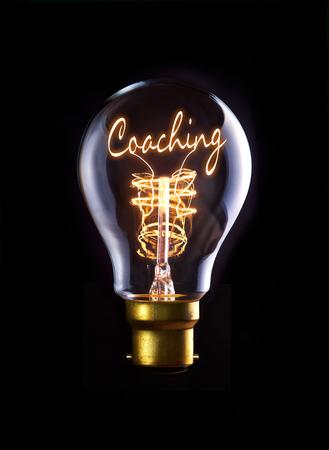Foto de Coaching concept in a filament lightbulb. - Imagen libre de derechos