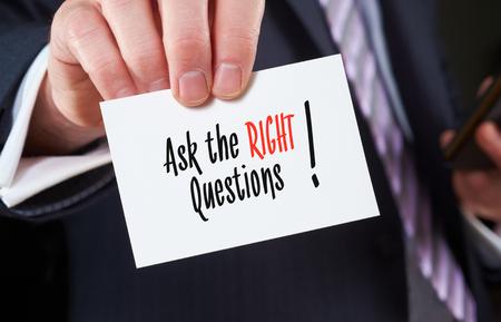 Foto de A businessman holding a business card with the words, Ask the Right Questions, written on it. - Imagen libre de derechos