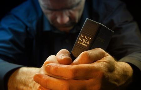 Photo pour A Man praying holding a Holy Bible. - image libre de droit