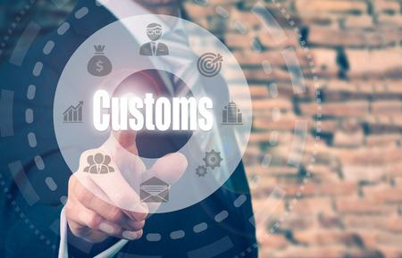 Foto de A businessman selecting a Customs Concept button on a clear screen. - Imagen libre de derechos