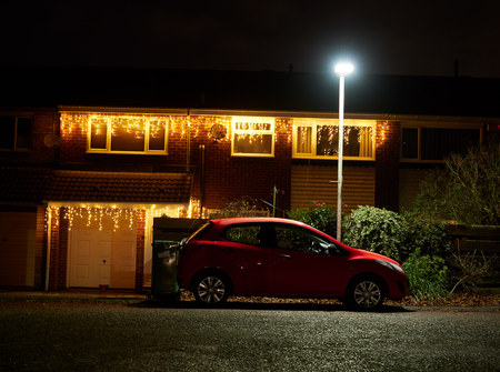 Photo pour A car sat under the security of a street lamp with Christmas lights on the house behind it. - image libre de droit